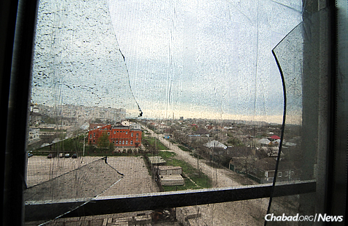 "A 2015 file photo of a smashed window in a Mariupol Jewish community member's apartment. The official death count was around 30, but Jewish community member Natasha Ralko—whose windows were blown out while she was in her living room with her daughter and 8-month-old infant, and whose kitchen was heavily damaged—was convinced that the number is higher. ""There were at least 30 bodies just down there around the parking lot,"" she said at the time. (Photo: Jonathan Alpeyrie for Chabad.org)"