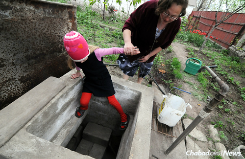 A 2015 file photo of Natasha helping her daughter into the garden bomb shelter in their yard. The family lives close to the fighting; their home has been rattled and their windows smashed in the last two weeks due to the intensification of fighting. (Photo: Jonathan Alpeyrie for Chabad.org)