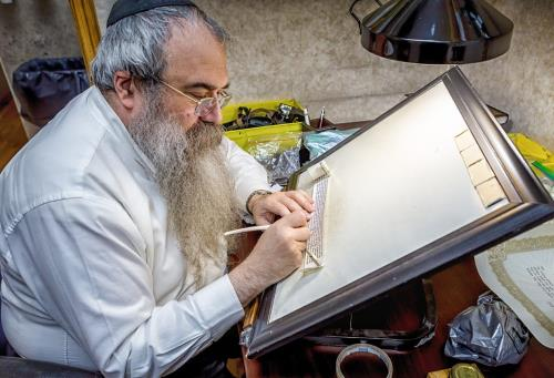 A trained scribe inspects a tefillin scroll (Photo: Eliyahu Parypa)