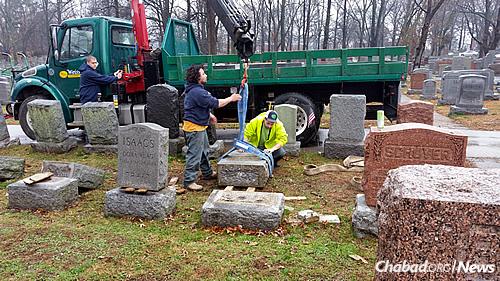 Cemetery workers begin repairing the damage.