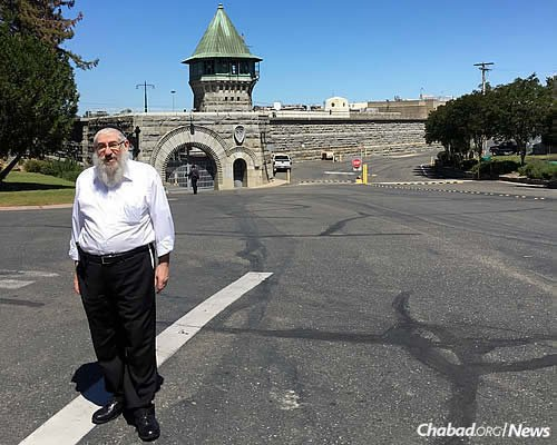 Rabbi Sholom Tenenbaum stands outside the famous Folsom State Prison in California during a visit to his daughter's Chabad center in that city. He now visits prisons in New York during Purim to celebrate the holiday with Jewish inmates.