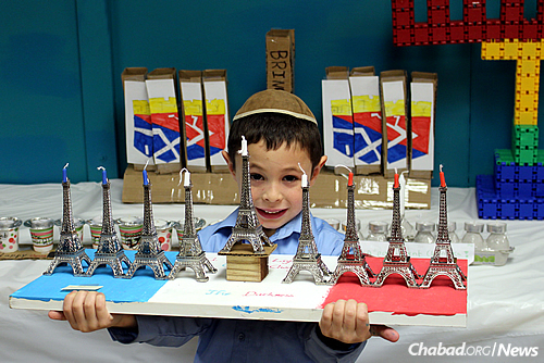 A student displays a Chanukah menorah with a decidedly Parisian theme.