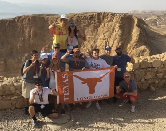 Students join Rabbi Zev Johnson to show their Longhorn pride atop Masada. June 2016