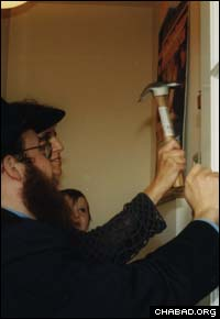 Rabbi Yossi Deren , a grandson of Risya Posner and co-director of Chabad-Lubavitch of Greenwich, Conn., assists in affixing a mezuzah on a Greenwich doorpost.