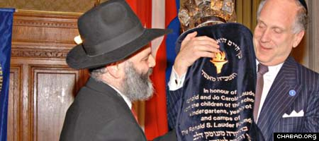 Businessman Ronald S. Lauder gets help holding a Torah scroll he received from Rabbi Jacob Biderman, chairman of Chabad-Lubavitch headquarters in Austria.