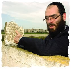 Raskin points out the hebrew inscription on a fragment of a tombstone