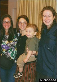Rivkah Holtzberg holds her son Moshe (center).