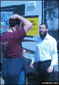 A Chabad-Lubavitch rabbinical student assists a Jewish attendee of last year's Berkshire Hathaway shareholders' conference lay tefillin.