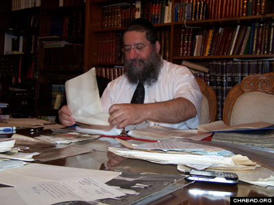 Rabbi Dovid Cohen with the letters his father-in-law, Rabbi Zeev Greenglass, received from the Rebbe. In the left corner is a letter from the Rebbe with blessings for a sweet new year.