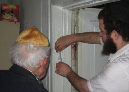 Helping an elederly Jew affix a mezuzah on his door. Note the box of matzah.