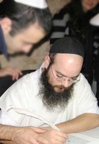 Assisted by ritual scribe Rabbi Shai Avramovitz, an Israeli pilot writes a letter in a new Torah scroll atop Masada.