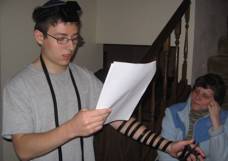 Jeff recites Shema, while wering tefillin for the first time, as his mother watches on.