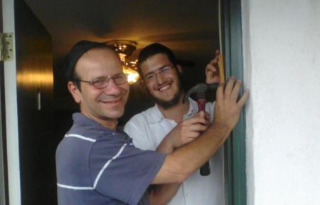 Helping someone install a new mezuzah.
