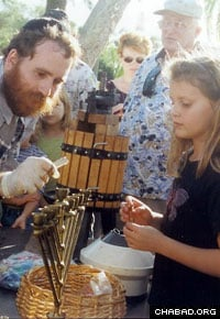 Rabbi Shlomo Uminer, director of the Chabad Jewish Center of Martin and S. Lucie County in South Florida, fills a Chanukah menorah with freshly-prepared olive oil.