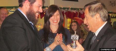 Chabad-Lubavitch of Orange County directors Rabbi Pesach and Chana Burston present a silver dreidel to County Executive Ed Diana.