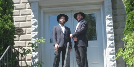 Mendy Singer and Mendy Dalfin standing at the entrance of the 100-year-old Congregation Bnai Zedek Chabad of Kenosha, WI.