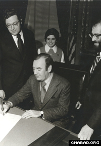 NY State Assemblyman Howard Lasher, Gov. Hugh Carey, and Rabbi Yisroel and Rochel Rubin mark the signing of a proclamation declaring Lubavitch Month in 1975. (Photo: Agudas Chasidei Chabad Library)