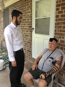 Joe Ribnick puts on tefillin.