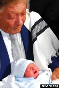 """2009: Sami Rohr reçoit l'honneur d'être sandak à la circoncision de son arrière-petit-fils Avraham Zvi Sragowicz à la synagogue """"The Shul of Bal Harbour"""" à Surfside en Floride."""