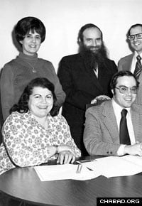 Miriam Gordon (standing, left) next to her husband Rabbi Sholom Ber Gordon, at a synagogue meeting in Newark, N.J., circa 1960s. (Photo: Lubavitch Archives)