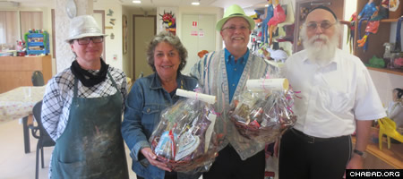 Special Purim gifts for visitors after a presentation by arts-department director Natali Charitonov, left, and Rabbi Zeev Crombie, director of the Grabski center.