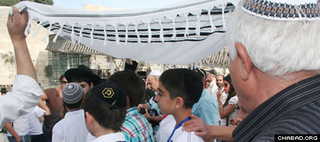 Last week, a group of 111 orphans celebrated their Bar Mitzvahs with a full program at the International Convention Center in Jerusalem, followed at the Kotel with the laying of <i>tefillin</i> and their first time being called up to the Torah. (Photo: Shohanah Shear)