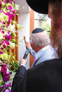 Affixing the mezuzah to the new Chabad building.