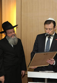 Bart De Wever, the mayor of Antwerp, presents a declaration in honor of Chabad of Antwerp. (Photo: Donald Woodrow)