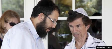 Rabbi Yossi Eber helps a local resident to don tefillin. (Photo: Melissa Gurdus Meiselman)