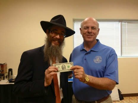 US Congressman Steve Pearce receives a two-dollar bill from Rabbi Levertov to pass on to charity.