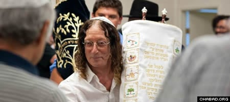 Stephen Cipes carries the newly written Torah scroll he donated to the Chabad center in Kelowna, British Columbia, Canada.