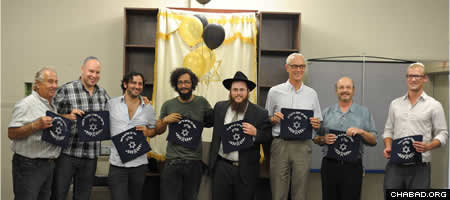 At the cermony, Rabbi Shmuly Hecht, center, honored community members who had bought a pair of tefillin (phylacteries) since Hecht arrived in Kelowna. Each received a blue tallit bag with their names inscribed in Hebrew on the outside.