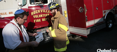 Tenenbaum assists Lenny Chornock, deputy fire chief of the Rockville Volunteer Fire Department, don tefillin. (Photo: Marc Asnin)