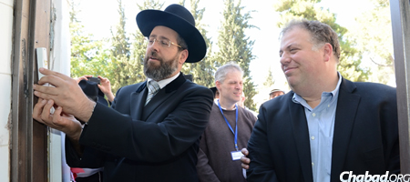 Israel's Chief Rabbi David Lau affixes the mezuzah to the main entrance of the new facility as philanthropist Daniel Fuchs, right, looks on.
