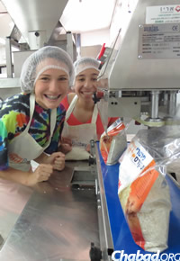 Young tourists join in the mitzvah of helping the needy by volunteering their time.
