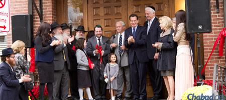 Rabbi Shua Rosenstein, center, cuts the ribbon at the dedication ceremony for the new Chabad on Campus center at Yale University. (Photo: Studio99Productions.com)