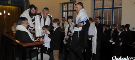 Sam Rachman's younger brother Joe, center, helps with the mitzvah of gelilah, dressing the Torah scroll before it is returned to the ark, as their father Jon Rachman, center right, looks on.