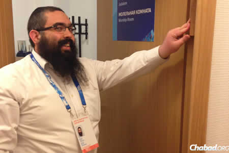 Rabbi Ari Edelkopf affixes a mezuzah at one of the two temporary Chabad Houses strategically placed near the 2014 Olympic Games.