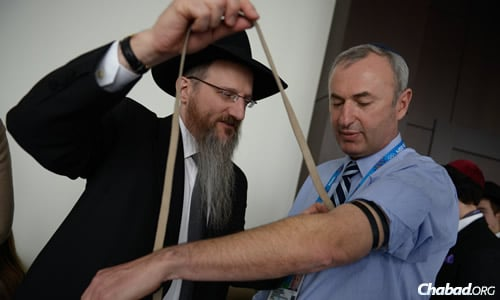 Rabbi Berel Lazar, the chief rabbi of Russia, helped Vladimir Shklyar, leader of the Israeli Olympic delegation, put on tefillin for the first time.