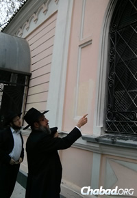 Chabad Rabbi Sholom Gotlieb, chief rabbi of Nikolayev, points to the damage.
