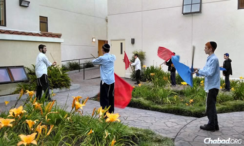 Boys practice flag maneuvers, which they will demonstrate in the Los Angeles parade, held near the Bais Chaya Mushka School.