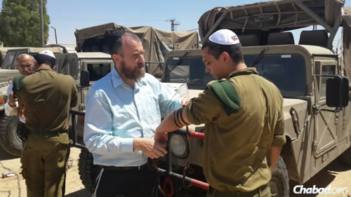 Chabad Terror Victims Project volunteers help combat soldiers don tefilln.