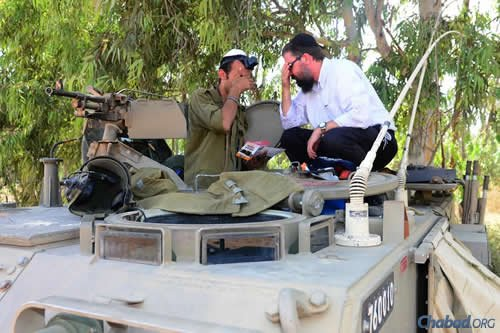 Rabbi Menachem Kutner, director of Chabad Terror Victims Project, prays with an Israel soldier.