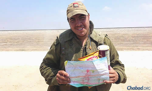 An IDF soldier displays a child's message, tucked into packages of food.