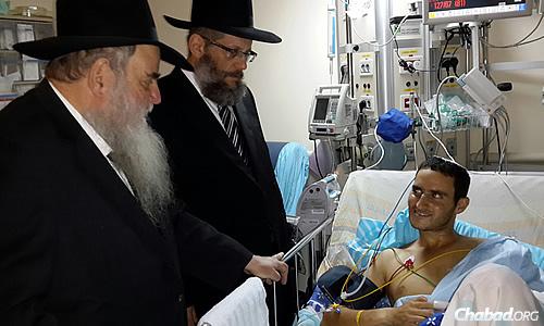 Rabbi Moshe Kotlarsky and Rabbi Yosef Yitzchak Aharonov with a wounded soldier.