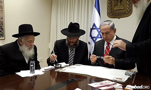 Aharonov, second from left, invites the prime minister to hold the feather and write a letter in the first verse of the Torah.
