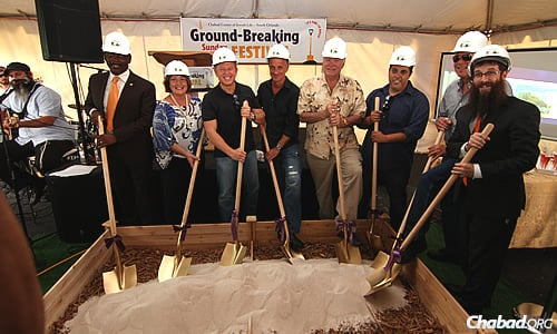 Helping dig into a new Chabad House in Florida are, from left, Orange County Sheriff Jerry Demings; Orange County Mayor Teresa Jacobs; Brett Kingstone, CEO Max King Realty; Julian Benscher, president, Skyship Services; David Siegel, CEO, Westgate Resorts; Richard Harary, CEO, Macrobaby; Dr. Abe Hardoon; and Rabbi Yosef Konikov, co-director of Chabad of South Orlando. (Photo: Sonacity Productions)