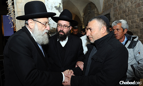 Rabbi Aryeh Stern, Ashkenazi chief rabbi of Jerusalem, greets a family member who came to a Chanukah menorah-lighting ceremony in honor of Israeli Defense Forces soldiers killed in the summer war with Hamas in Gaza. Next to them is Rabbi Menachem Kutner, director of the Chabad Terror Victims Project, which invited the families. (Photo: Mendy Hechtman)