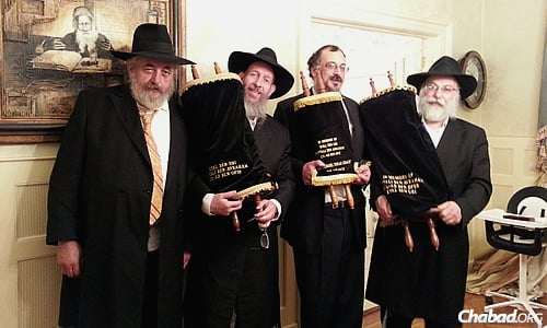 These Torahs were commissioned in honor of the three Israeli teenage boys abducted and killed by Palestinians this past June. Holding them, from left, are Yankel Yankelowitz; Bentzion Chanowitz, who runs the Torah Gemach, a project of Merkos Suite 302; Yerachmiel Paskin; and sofer (Torah scribe) Rabbi Daniel Dovid Dahan.