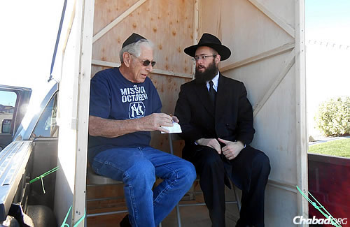 Offering a man a bite to eat in the sukkah; the rabbi also brought with him a lulav and etrog to shake, all of which are traditions associated with the eight-day holiday